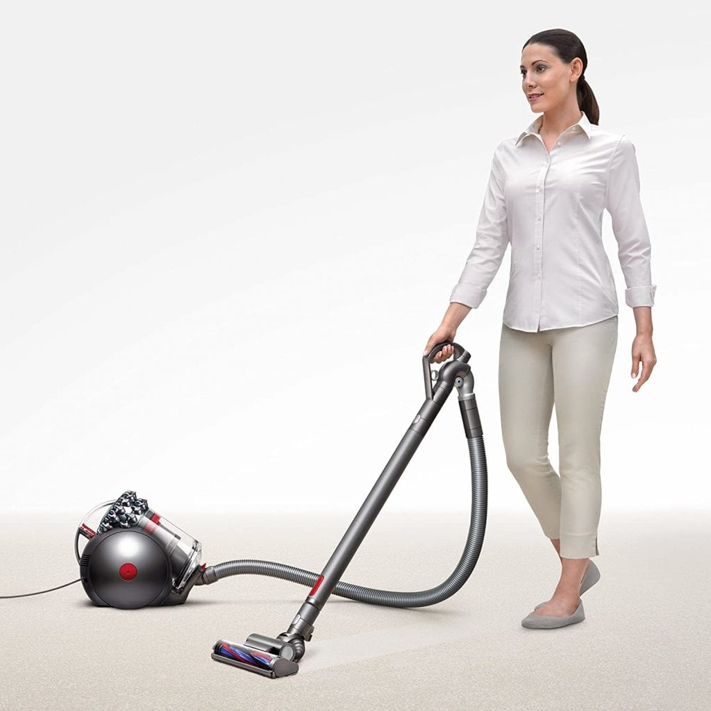 Woman is vacuuming a dog hair on the carpet with Dyson Cinetic Big Ball Animal Canister